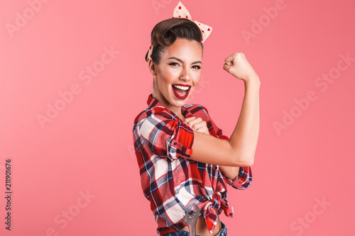 Fototapeta Gorgeous strong young pin-up woman showing biceps. obraz
