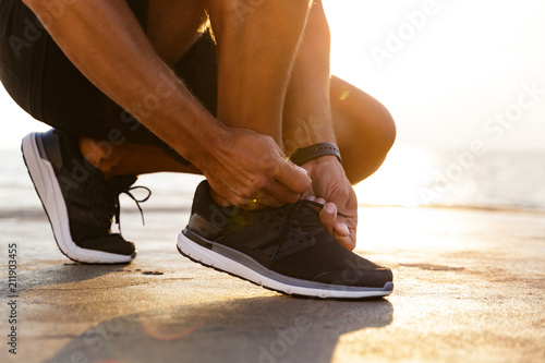 Fotografia  Cropped photo legs of sporty caucasian man in tracksuit and sneakers squatting o
