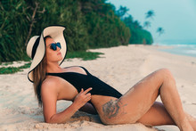 Close-up Of A Young European Girl Lying On A White Beach, Sunbathing, Slender Legs All In The Sand, Wearing A Black Bikini Swimsuit, Pulling Him Up Above The Hips, Showing Her Sexy Tattoo