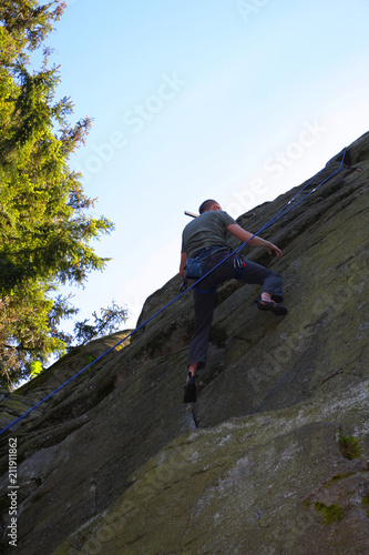 Young man is climbing outdoor on a rock with a rope