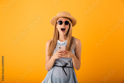 Portrait of an excited young blonde woman in summer hat