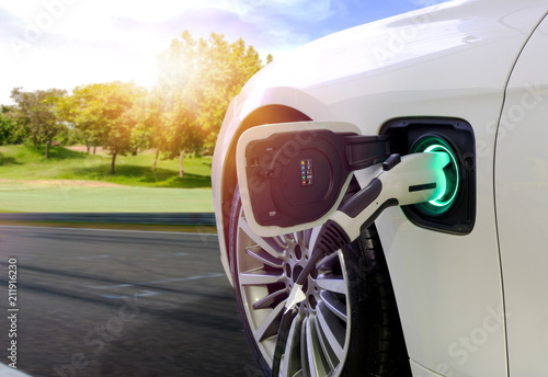 Foto  EV Car or Electric car at charging station with the power cable supply plugged in on blurred nature with soft light background