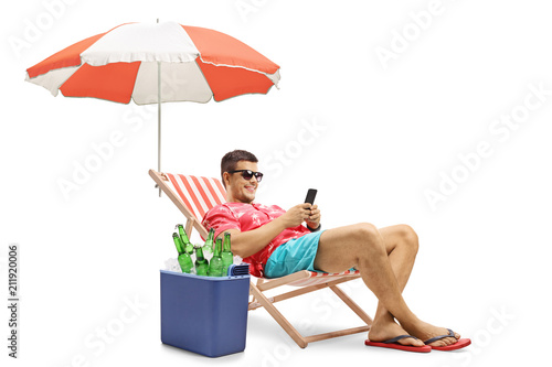 Stampa su Tela Tourist with a phone sitting in a deck chair with an umbrella next to a cooling