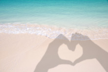 Shadows Of Hands Forming A Heart On Sand And Caribbean Beach Background