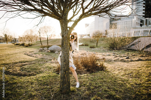 Portrait of a beautiful young blond woman with a camera, lifestyle