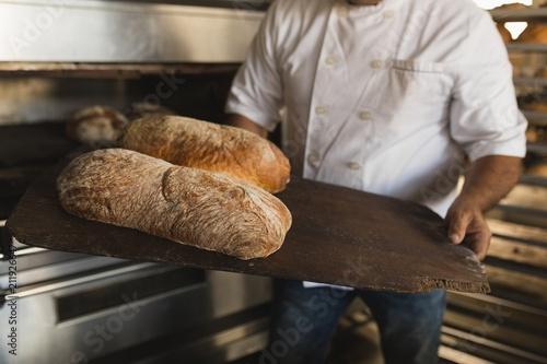 Male baker holding baked bread in bakery shop