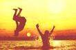 Leinwandbild Motiv Glückliche junge Menschen laufen und springen am See beim Sonnenuntergang