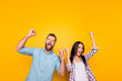 Leinwanddruck Bild - Portrait of crazy man couple full of happiness yelling loudly holding raised arms keeping eyes closed celebrating victory isolated on vivid yellow background