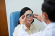 Crop ophthalmologist putting special glasses with trial lens on mature Asian woman testing eyesight
