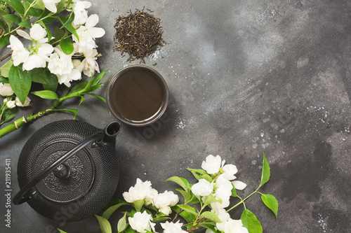 Green jasmin tea and jasmine flowers, cup of green tea on black Canvas Print