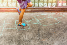 Child Playing Hopscotch Game On Concrete Floor Outdoors
