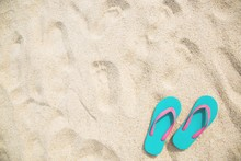 Sea On The Beach Footprint  People On The Sand And Slipper Of Feet In Sandals Shoes On Beach Sands Background. Travel Holidays Concept.