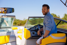 Proud Owner. Pleasant Young Man Posing Behind A Steering Wheel Of A Yacht And Smiling, Being Proud Of His Purchase