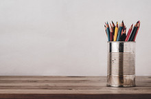 Coloured Drawing Pencils In Metal Tin On Wood Plank Desk