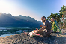 Friends Relaxing On Mountain Ledge Overlooking Lake, Squamish, Canada