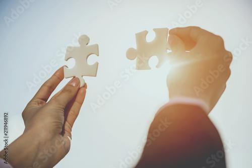 Fotografie, Obraz  Close up. Hands of Businesspeople Solves Puzzle.