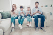 Leinwandbild Motiv Portrait of family with two kids having holding smart phone electronic device in hands texting sms using wi-fi 5G internet checking email searching contact. Apps concept