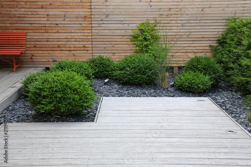 Fotobehang Tuin Moderne Garten- und Terrassengestaltung: Terrasse aus Holz und Pflanzen im pflegeleichten Schotterbett vor einer Holzwand