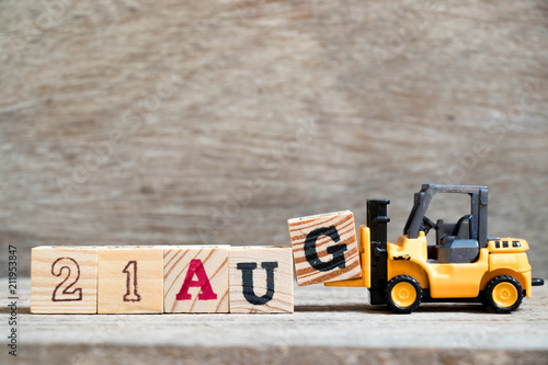 Poster  Toy forklift hold block G to complete word 21 aug on wood background (Concept fo