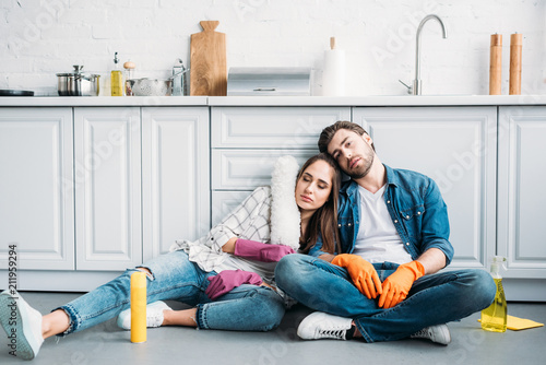 Fotografie, Obraz  tired couple sitting on floor and leaning on kitchen counter after cleaning in k