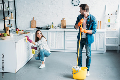 Fotografia  happy couple cleaning kitchen together and looking at each other