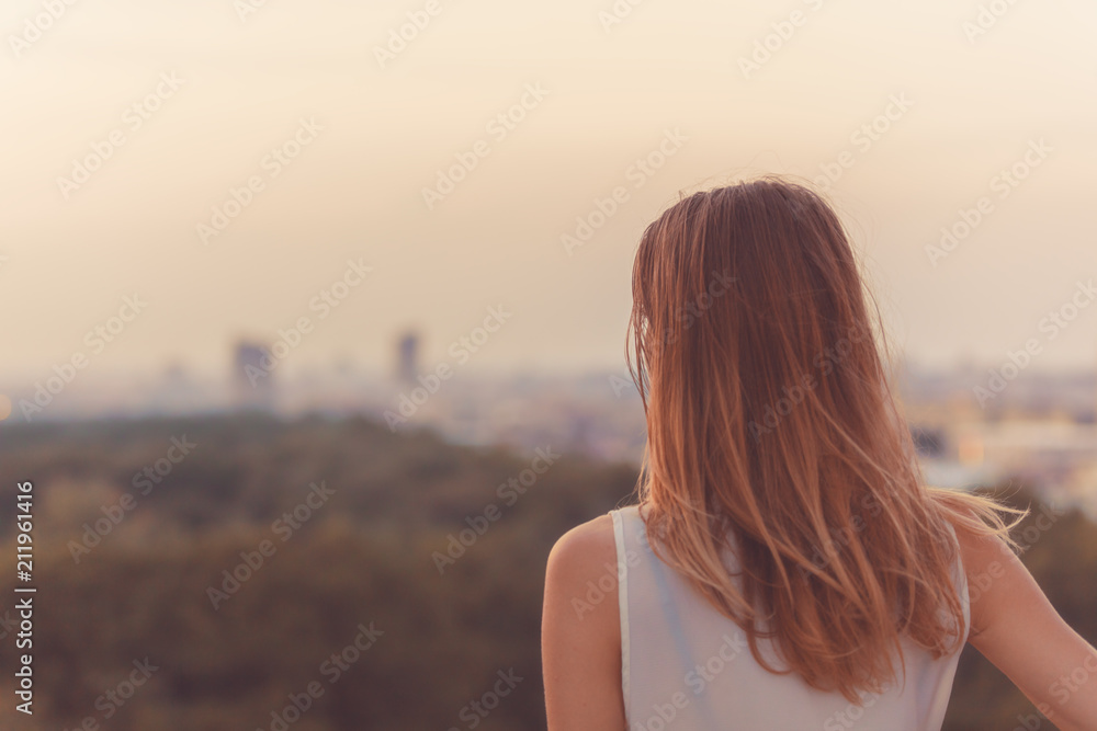 Fototapeta Single woman looking at the distant city landscape.