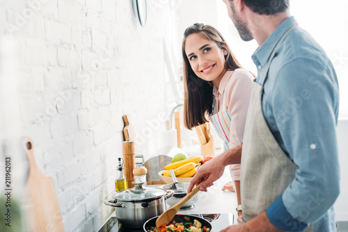 Fototapeta boyfriend frying vegetables on frying pan in kitchen and looking at smiling girlfriend obraz