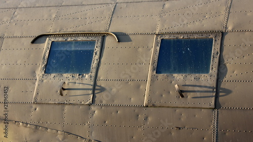 Photo  Two side windows of Douglas Dakota DC-3 C-47 WWII steel war plane exhibit in loc