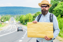 Man Bearded Hitchhiker Stand At Edge Of Road With Blank Paper Sign, Copy Space. Benefits Using Sign With Name Destination. Cardboard Sign With Indication Where You Want Go. Short General Directions