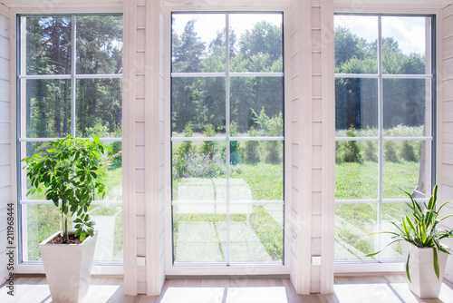 Bright interior of the room in a wooden house with a large window overlooking the summer courtyard Fototapeta