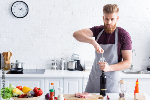 handsome bearded young man in apron opening bottle of wine and looking at camera while cooking in kitchen