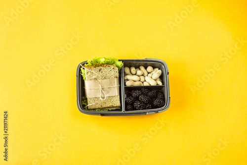 Poster Assortiment Lunchbox with food - sandwich, nuts and berries on a yellow background. Top view, flat lay,