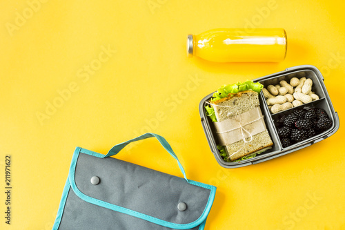 In de dag Assortiment Lunchbox with food - a sandwich, nuts and berries - next to a bottle of orange juice and a bag for a luncheon. Food you can take with you. Top view, flat lay,
