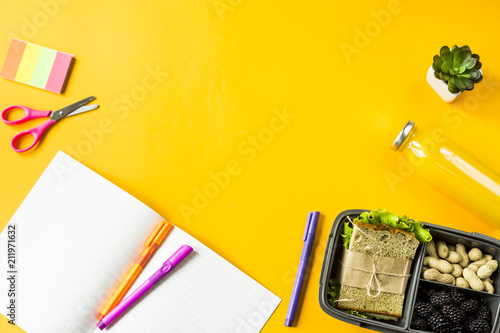 Poster Assortiment Lunchbox with food - a sandwich, nuts and berries - stands next to the notebook, pens and other supplies for study. Meals between lessons. Top view, flat lay, copy space