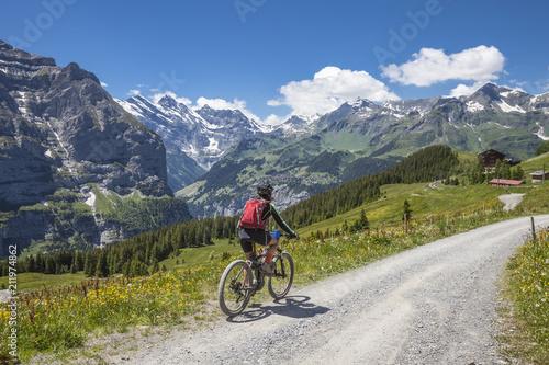 Deurstickers Fietsen nice senior woman, riding her e-mountainbike on the Lauberhorn downhill from Kleine Scheidegg to Wengen and Lauterbrunnen,Jungfrauregion,Switzerland