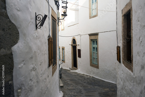 Deurstickers Smal steegje A view of a narrow street with arch and wooden windows and doors with white wall stone architecture of the island Patmos, Greece