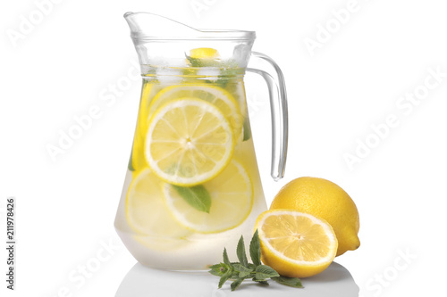 Vászonkép Homemade lemonade with mint and ice in a glass jug and a glass next to fresh lemon on a white background