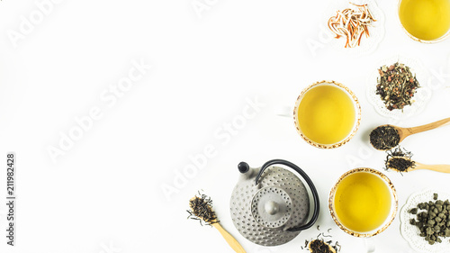 Fotografía  Gray iron kettle among different kinds of dry tea and cups with a ready drink on a white table