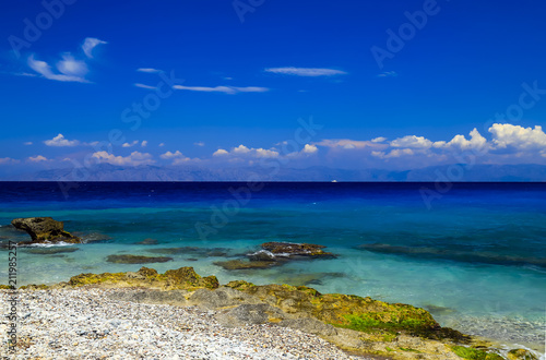 Picturesque summer beach, pebbles in the surf line on a