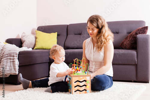 Fototapety, obrazy: Beautiful young mother playing with her small son on floor