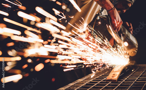 Poster de jardin Metal Worker Using Angle Grinder in Factory and throwing sparks