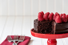 Chocolate Cake With Red Raspberries On Top, And A Slice Take Out, On A Red Cake Platter, And Three Forks On A Red Napkin, Against A White Background