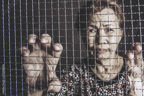 網目をつかむ高齢女性 Fototapeta