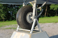Right Tire Of Douglas Dakota DC-3 C-47 WWII Plane Exhibit In Local Forest Positioned On Stone And Steel Foundations