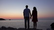 Romantic couple standing on rocky shore admiring sunset over sea