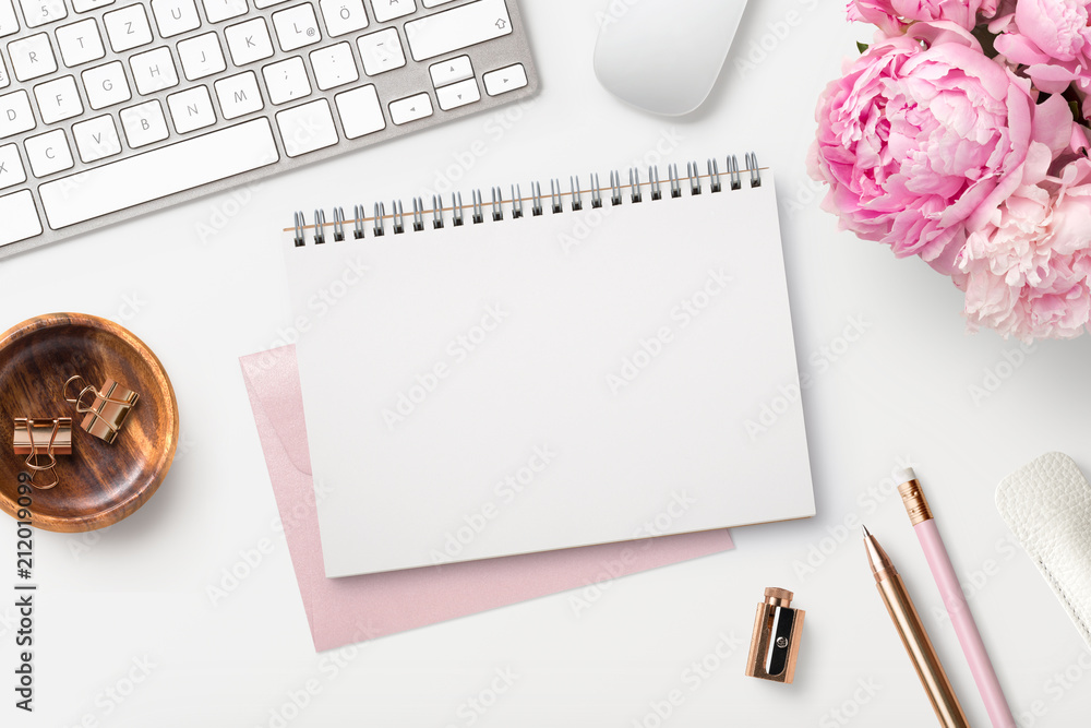 Fototapeta feminine workspace / desk with blank open notepad, keyboard, stylish office / writing supplies and pink peonies on a white background, top view