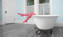 Legs In Red And White Striped Tights Hanging Over Edge Of Antique Bath Tub In Blue, Vintage Bathroom