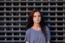 Sad Girl In Front Of Metal Grid, Teenager Prisoner Or Abuse Victim