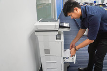 Businessman Put Blank Paper Stack Into Office Printer Tray For Copying Documents