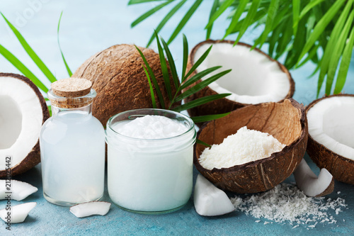 Set of natural coconut products for spa treatment, cosmetic or food ingredients decorated palm leaves. Coconut oil, water and shavings.